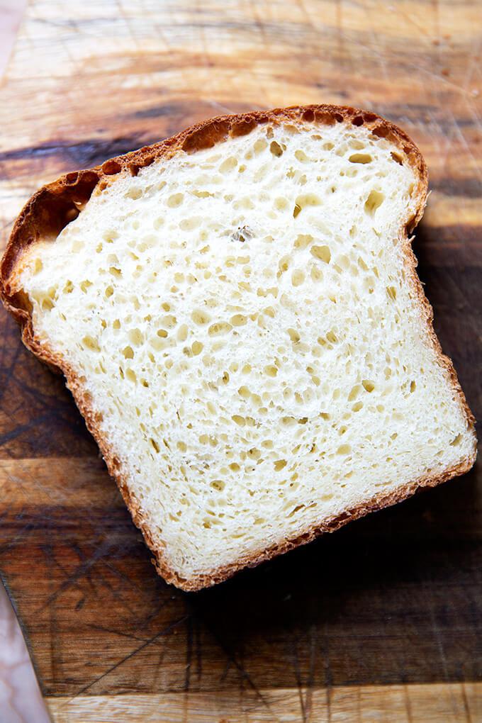 A slice of brioche bread on a cutting board.