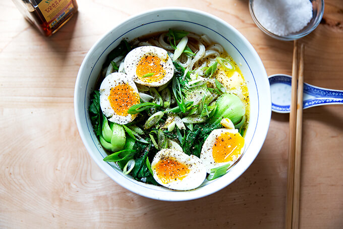 A bowl of life changing udon noodles with bok choy and soft boiled eggs.