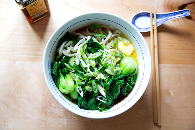 A bowl of life changing udon noodles with bok choy.