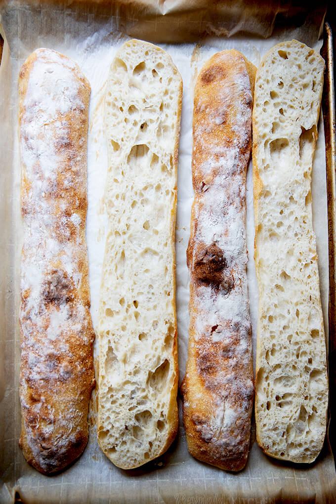 Halved sourdough ciabatta baguettes on a sheet pan.