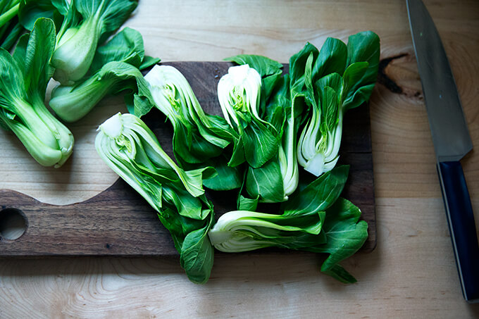 A board topped with halved bok choy.
