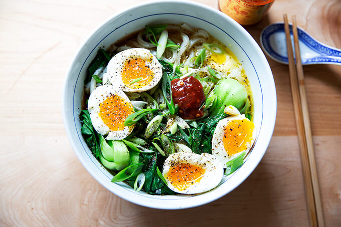 A bowl of life changing udon noodles with bok choy and soft boiled eggs and Sambal Oelek.
