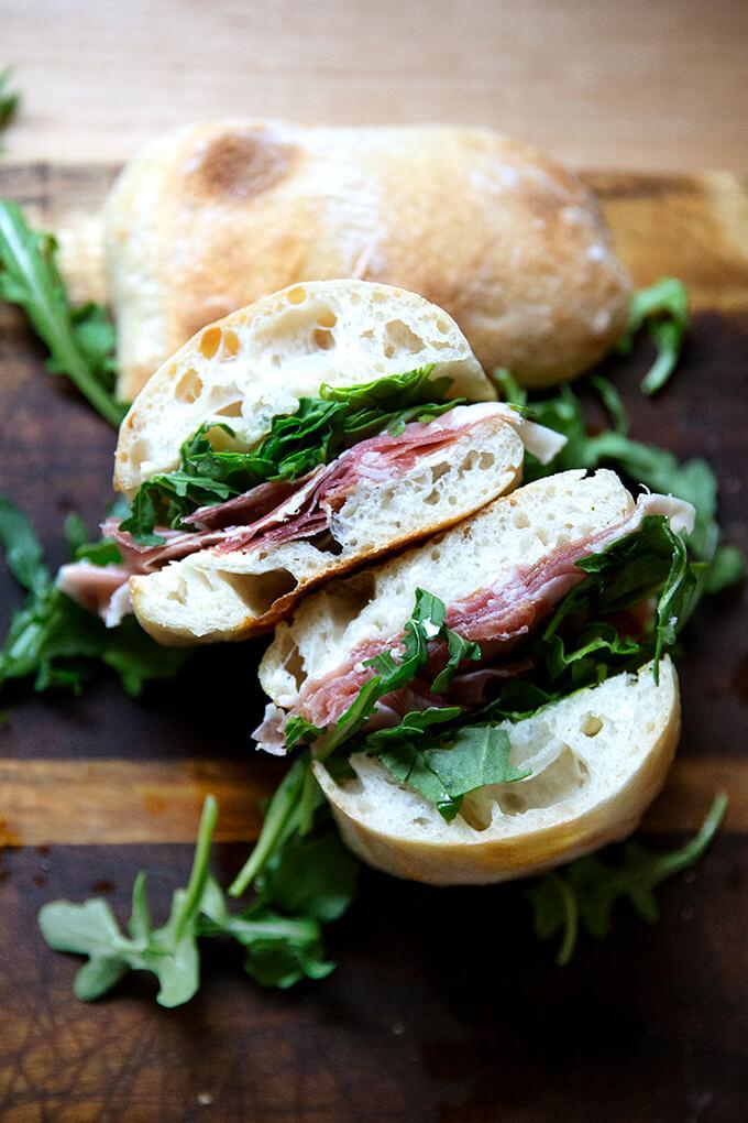 A halved prosciutto and arugula sandwich.