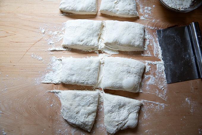 Portioned sourdough ciabatta rolls on a countertop.