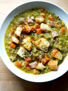 A bowl of split pea and ham soup topped with olive oil croutons.