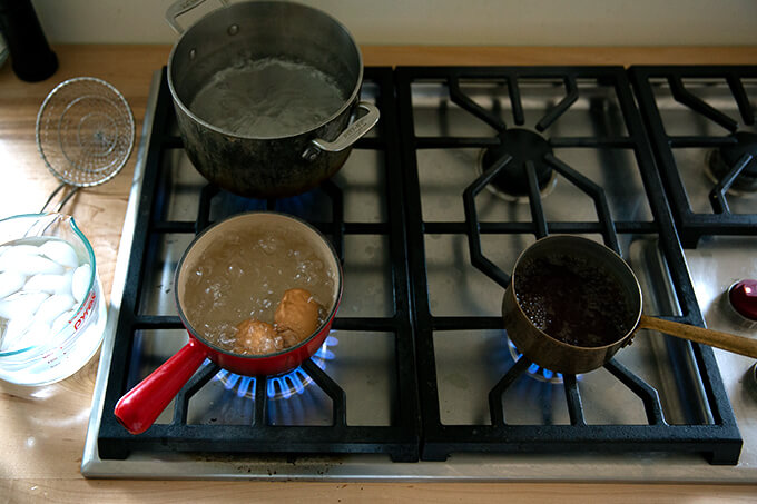 A stove top with three pots boiling away.