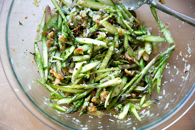 A bowl of raw asparagus salad all tossed together.