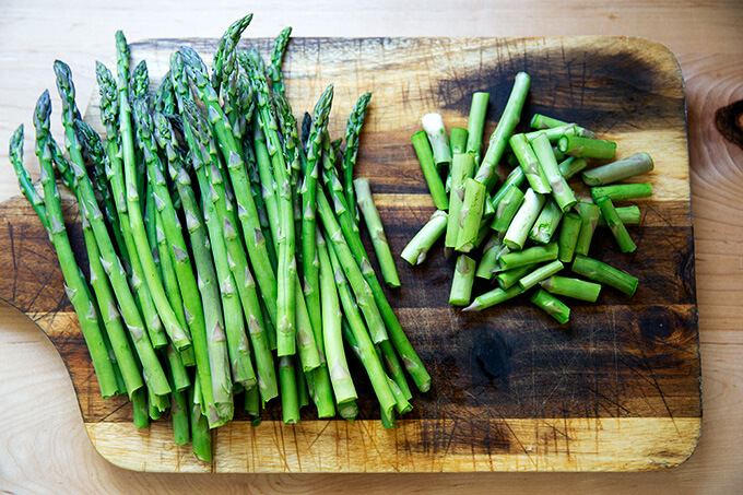 Asparagus, on a board, ends snapped off.