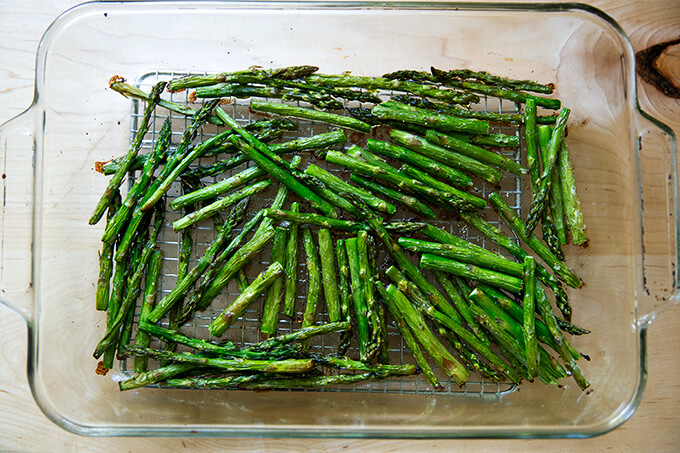 Roasted asparagus in a 9x13-inch glass baking dish.