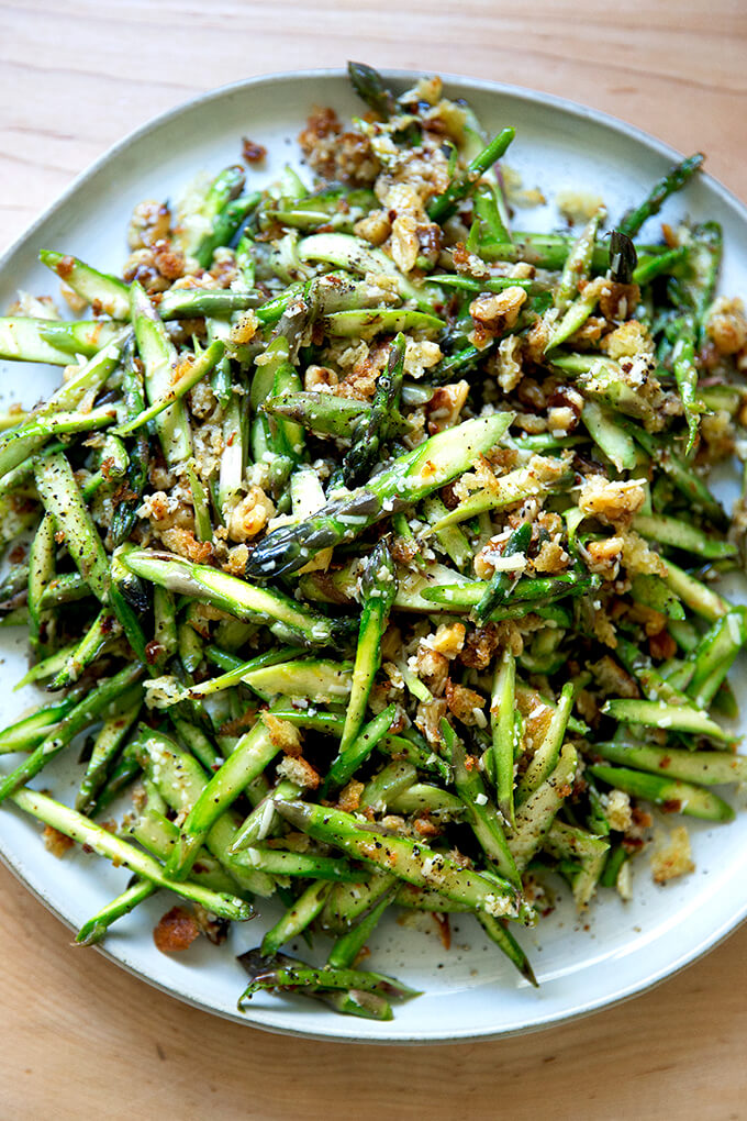 A raw asparagus salad on a platter.