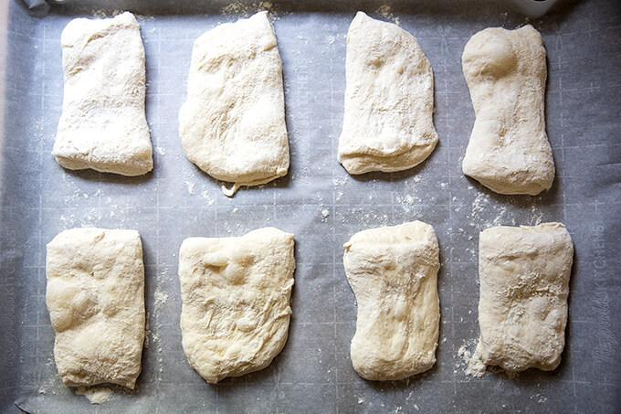 Shaped ciabatta rolls unbaked on a sheet pan.