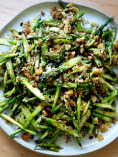 A raw asparagus salad on a platter.