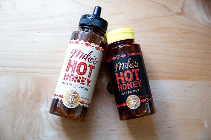 Two bottles of Mike's Hot Honey on a counter top.