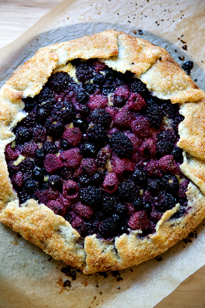 Just-baked mixed berry galette on a board.