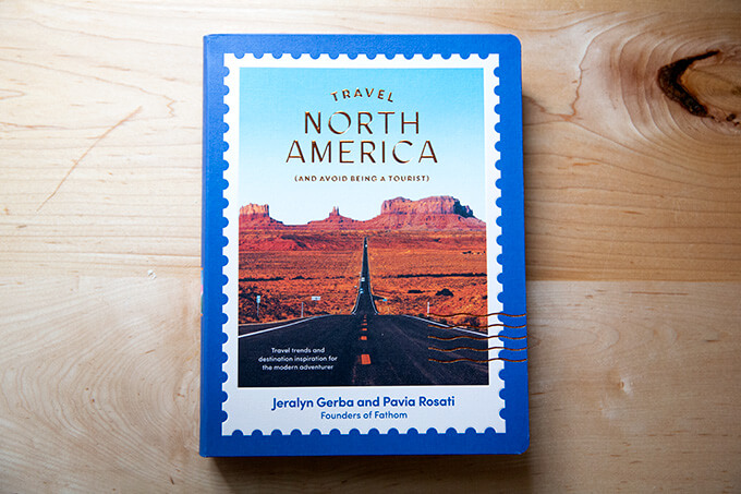 A book, Travel North America, on a counter.