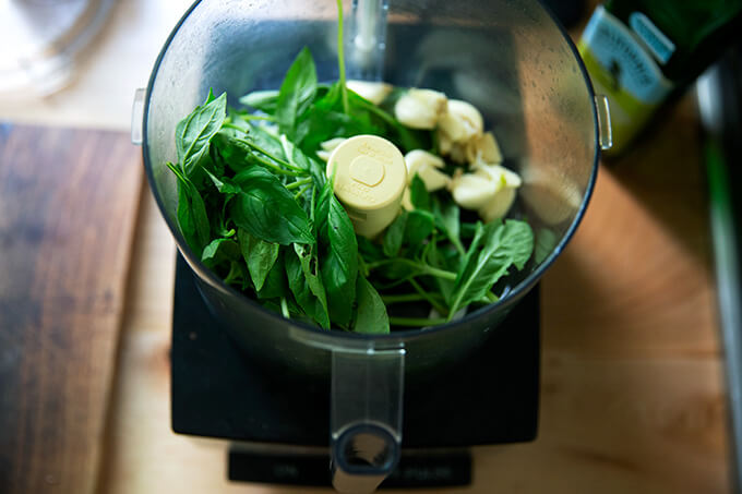 A food processor with garlic and basil.