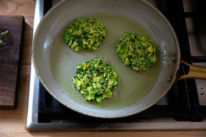 Zucchini fritters frying in a frying pan.