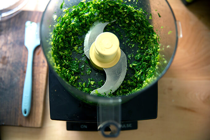 A food processor with pulsed basil and garlic.