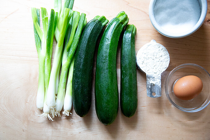 Scallions, zucchini, flour and an egg, the ingredients to make zucchini fritters, on a board.