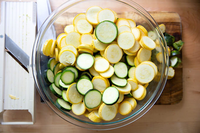 Sliced zucchini and summer squash in a large bowl aside a mandoline.