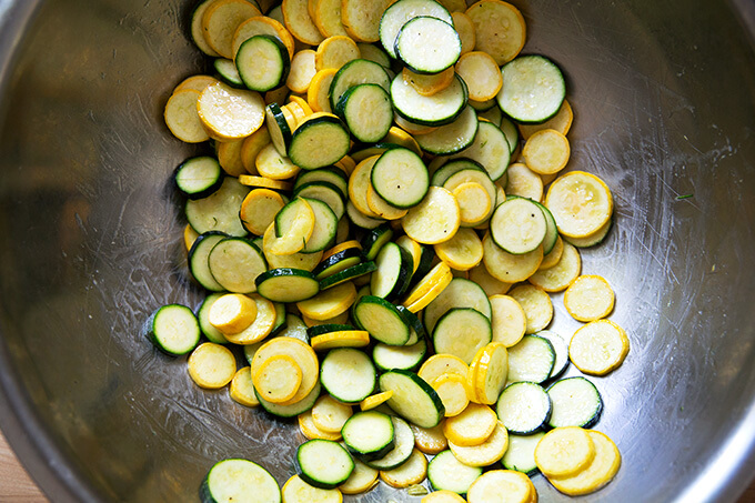 Sliced summer squash and zucchini in a large bowl dressed with olive oil and salt and pepper.
