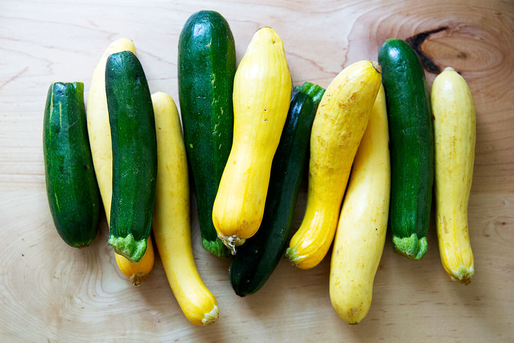 A pile of zucchini and summer squash on a countertop.