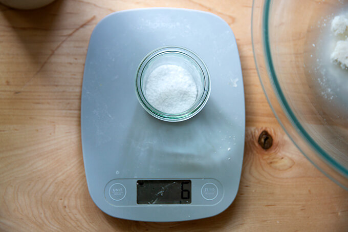 A scale with 6 grams of salt measured in a small glass jar on top.