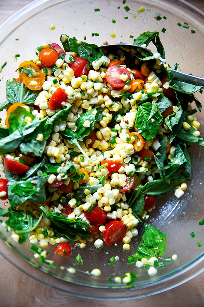 A raw corn salad made with tomatoes and lots of herbs all tossed together in a bowl.