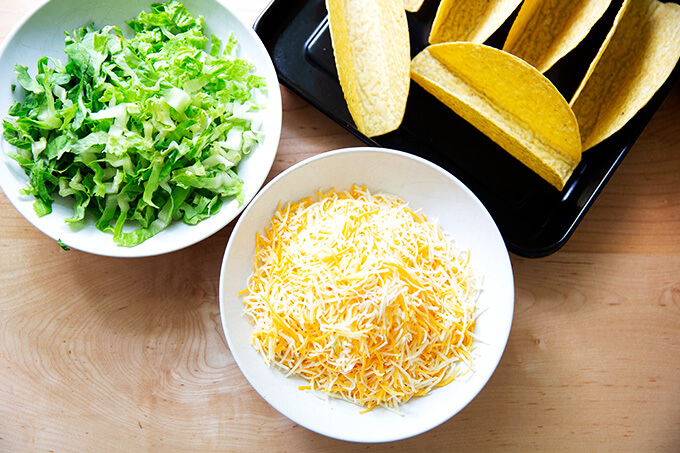 Grated cheese and lettuce in a bowl.