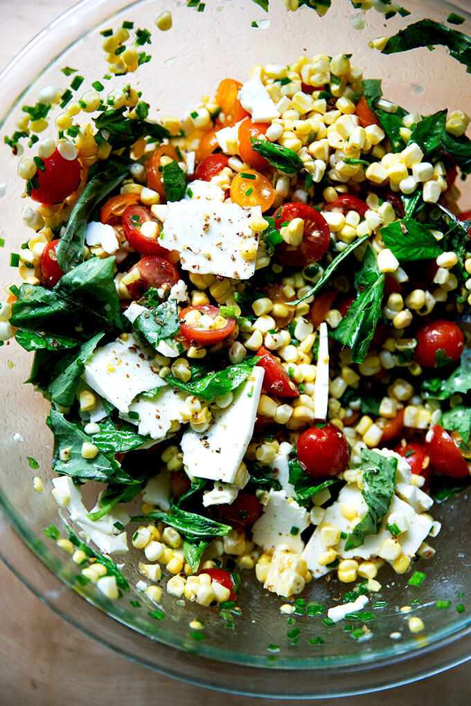 A raw corn salad made with tomatoes, feta, and lots of herbs all tossed together in a bowl.