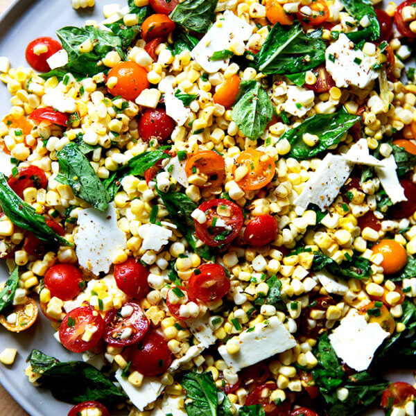 A platter topped with a raw corn salad made with tomatoes, feta, and lots of herbs.