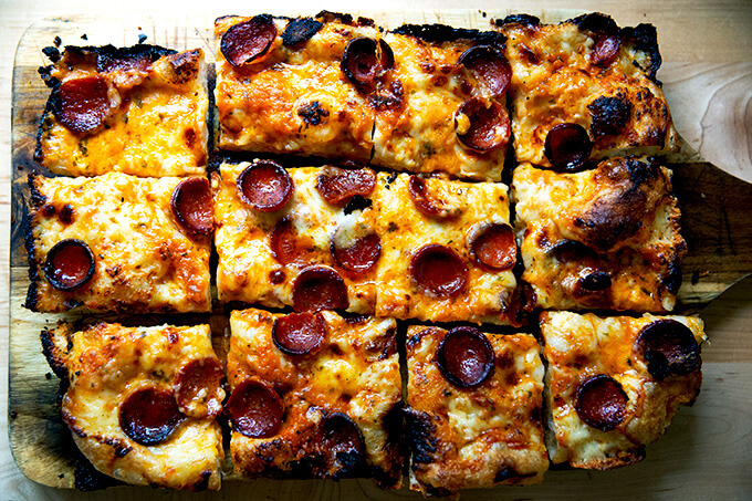 A sliced pepperoni Detroit-style pizza on a board.