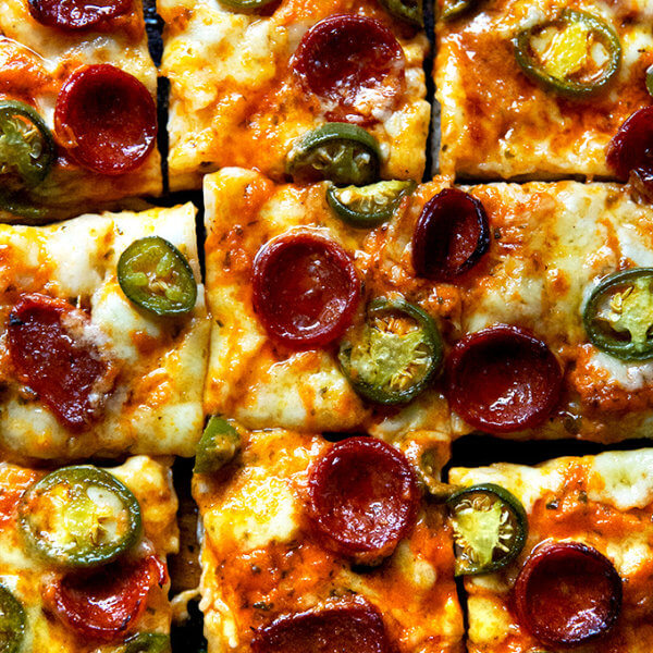 A sliced pepperoni and pickled jalapeño Detroit-style pizza on a board.