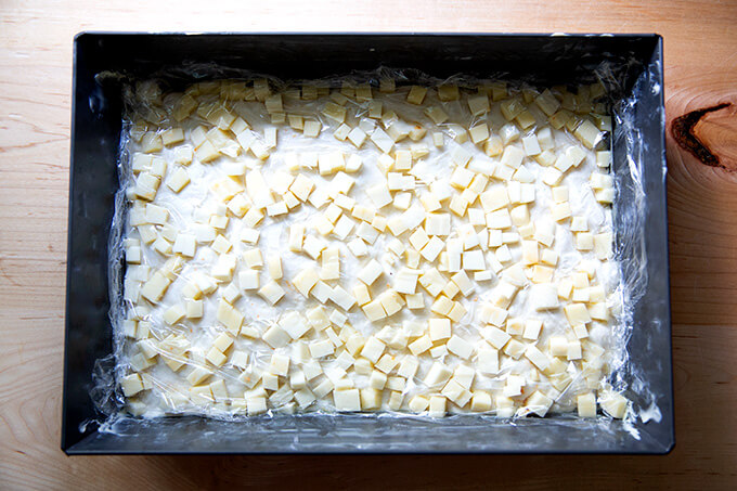 A pan filled with Detroit pizza dough, topped with cubed cheese, and a layer of plastic wrap.