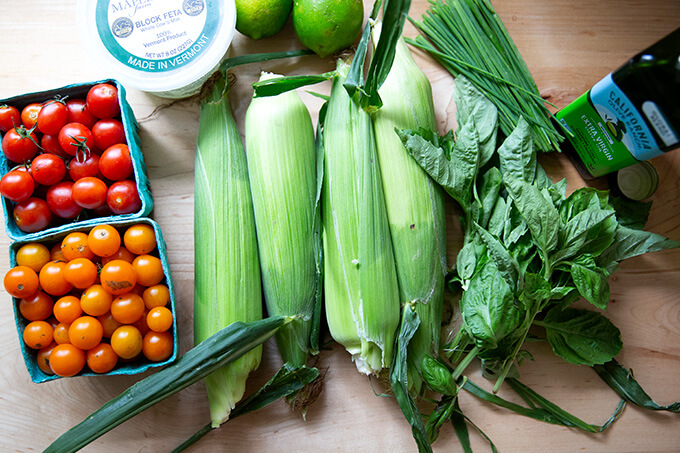The ingredients to make a raw corn, tomato, and feta salad on a countertop.