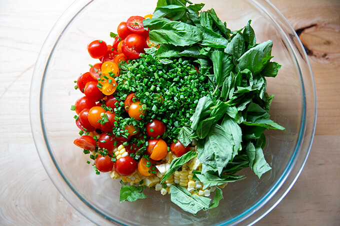 A bowl filled with the ingredients to make a raw corn salad made with tomatoes, feta, and lots of herbs.
