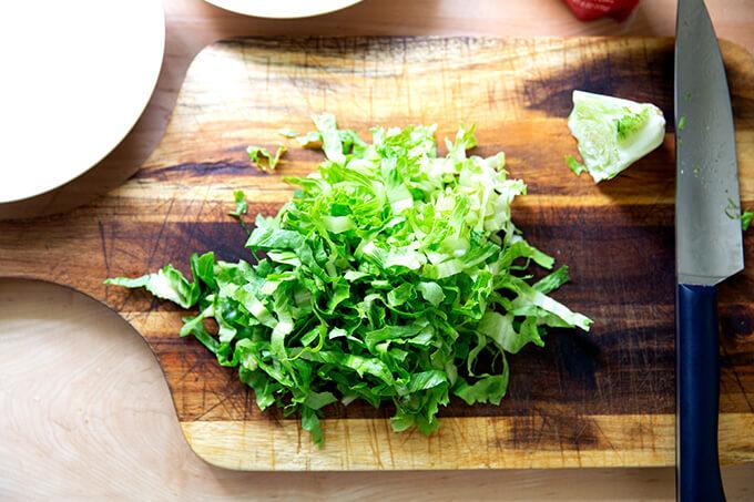 A head of Romaine lettuce on a cutting board, shredded.