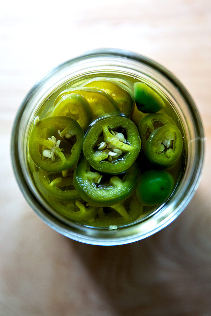 An overhead shot of a jar of pickled jalapeños.