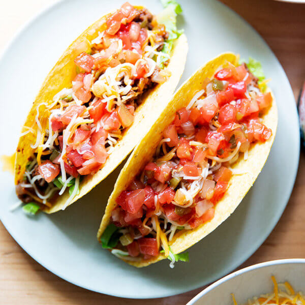 Two hard shell tacos filled with taco meat, cheese, and salsa on a plate.