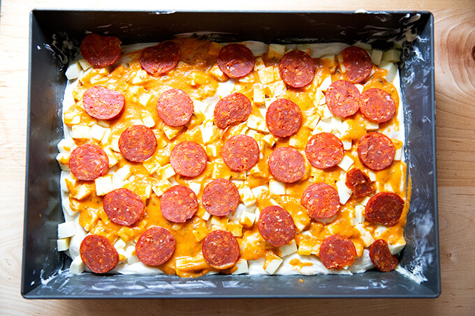A pepperoni Detroit style pizza ready for the oven.