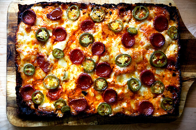 A just-baked pepperoni and pickled jalapeño Detroit-style pizza on a board.