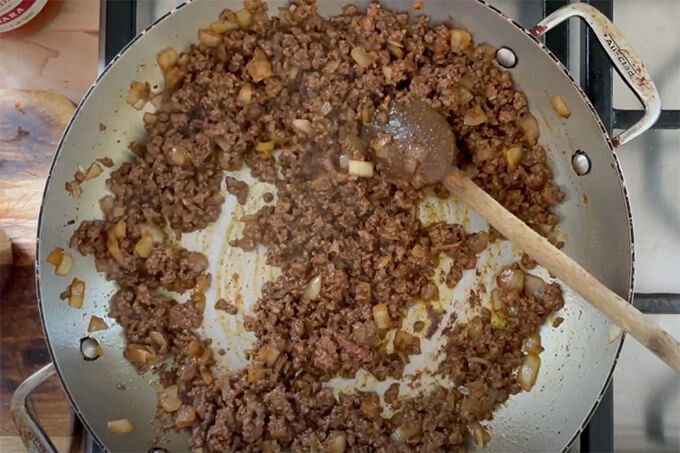 A sauté pan filled with onions, taco seasoning and ground beef.