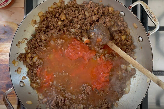 A sauté pan filled with taco meat ready to simmer.