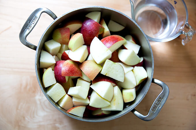 A pot holding chopped up apples aside a liquid measure holding a cup of water.