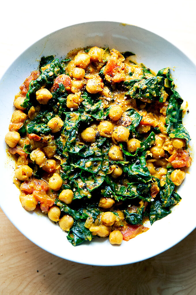 A bowl of curry-spiced chickpeas, tomatoes, and kale.