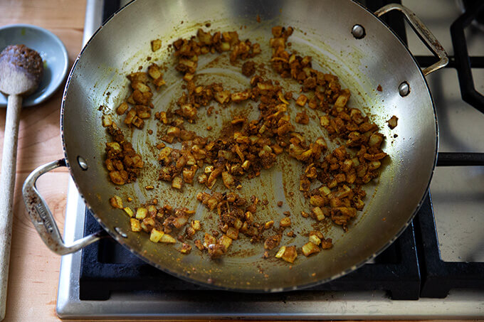 A skillet on the stovetop holding curry spiced onions, garlic, and ginger.