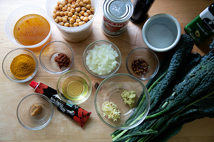 The ingredients to make spicy chickpeas with tomatoes and kale.