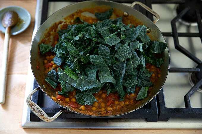 A skillet on the stovetop holding stewy chickpeas and tomatoes with a heap of kale on top.