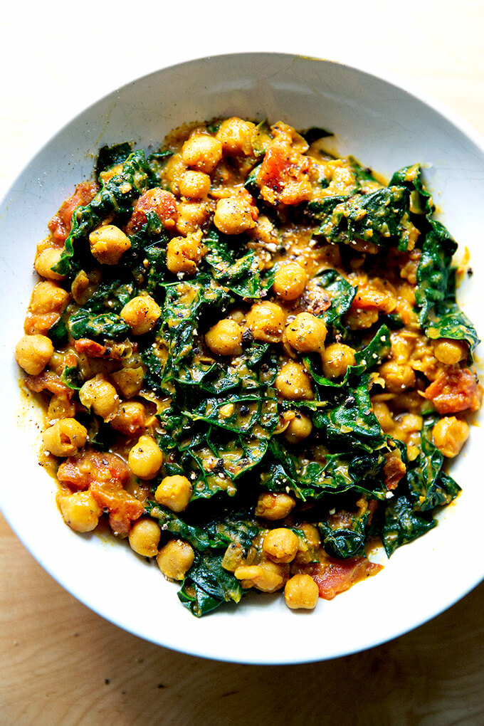 A bowl of spicy chickpeas with tomatoes and kale.