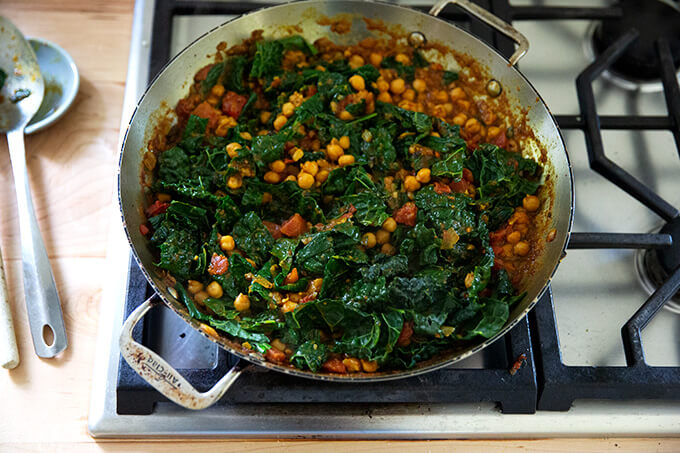 A skillet holding curry spiced chickpeas, kale, and tomatoes.